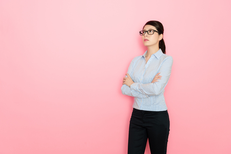 business lady standing on pink background thinking and looking on blank pink space