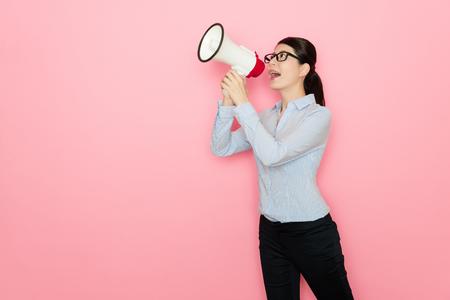signora di affari utilizzando altoparlante parlando isolato su sfondo rosa