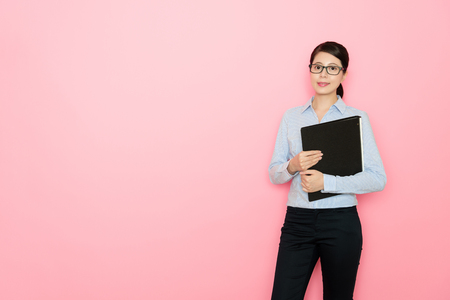 business girl standing on pink background holding a file document Stock Photo