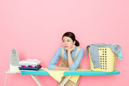 housewife feel bord to do the housework laundry ironing isolated on pink background.