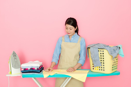 charming Japanese woman checking the clean clothing on ironing board and doing the laundry work on pink background