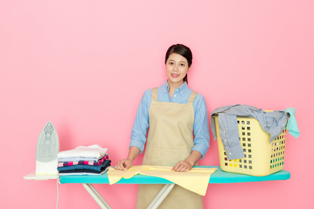 beautiful Asian woman doing the ironing with iron board smiley face to the camera isolated on pink background