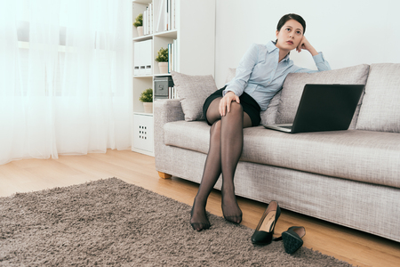 young Japanese business girl feels tired to working at home take rest sitting on the sofa.