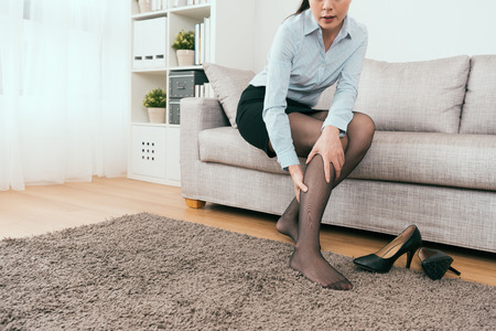 businesswoman sitting on the sofa feel the leg cramp after back from the work. Stock Photo