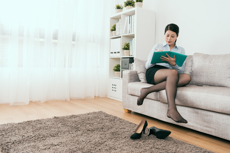 Japanese businesswoman sitting on the sofa writing note take off her high heel in the living room at home