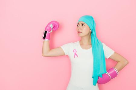vrouwelijke patiënt die de bokshandschoenen draagt die de machtsarm en de uitdaging tonen. Stockfoto