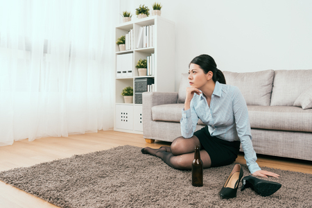 businesswoman manager is drinking away her sorrow from work and sitting on the floor of the living room at home