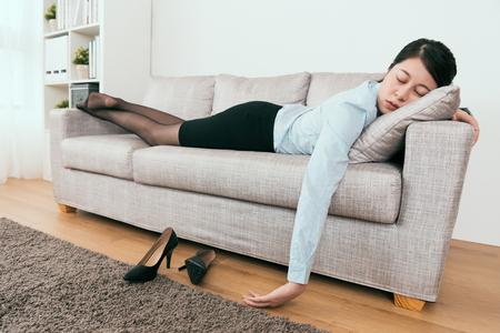 彼女は仕事から非常に疲れていて、一日中仕事の後にソファで眠りに落ちる 写真素材 - 107200399