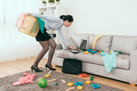 beautiful Japanese businesswoman is using notebook reply the E-mail and cleaning up the mess toys and clothes at home.