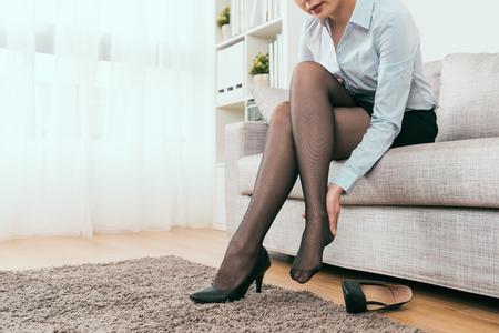 Geschäftsfrau zu Hause und fühlen sich nach dem Spaziergang mit Schuhen mit hohen Absätzen schmerzhaft an der Fußferse Standard-Bild
