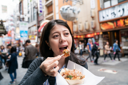 asian visitor eating takoyaki happily. a kind of japanese cuisine. tying oriental food curiously Stock Photo