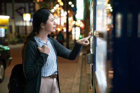 asian female looking for what to drink. standing in front of a vending machine.