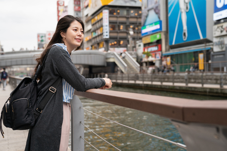 beautiful asian woman standing at the river. feeling relaxing and looking at somewhere. leaning on the guardrail.