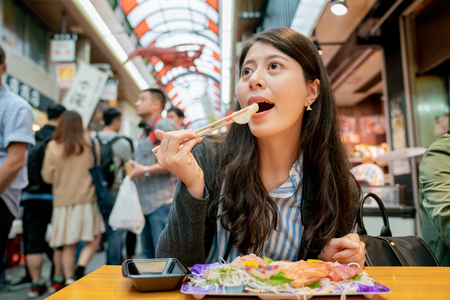 asian female eating sashimi in the market. a plate of raw fish and view from crowds.