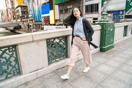 asian female strolling in the street. relaxing and putting hand in the pocket. by the background of the Dotonbori river. Stock Photo