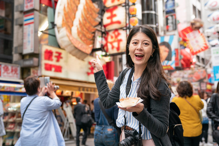 asian female visiting the landmark in japan. pointing to shops and laughing pleasantly.