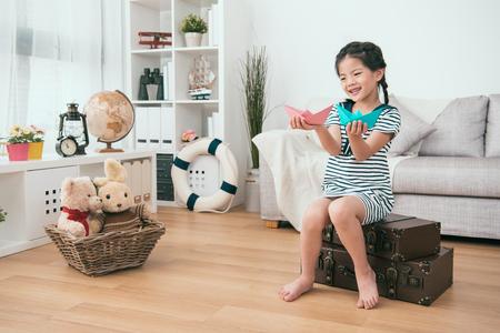dziecko trzyma w rękach papierowe statki. Wydaje się radosna i zadowolona.