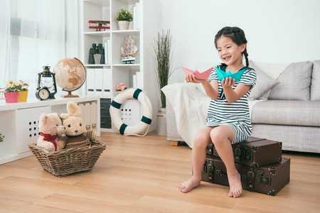 kid holding paper ships in her hands. She seems joyful and content.