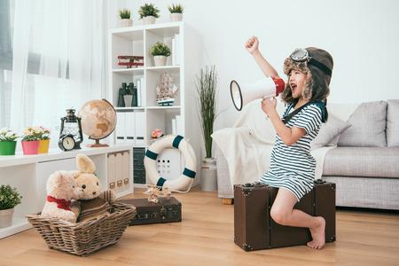 enfant tenant un mégaphone et levant la main. elle est prête pour le prochain tour