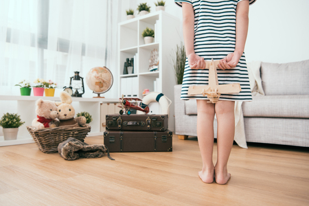 kid standing and putting her arms behind the back. Carefully holding her toy.