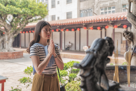asian woman praying faithfully in Longshan Temple. a traditional ritual in chinese culture.