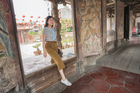 pretty asian woman walking into Longshan Temple Taiwan. She's sightseeing with joy. Stockfoto