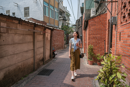 asian woman walking in the narrow alley. surrounding in the old houses.