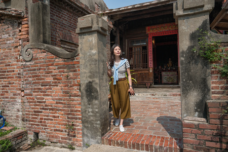 standing in the old tranditional house. asian woman visiting one of the oldest house.