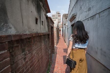 visitor standing in the narrow alley. view from back.