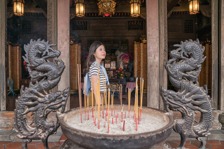 asian woman standing in the temple. Finishing the ritual for worshiping gods. 写真素材
