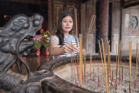 believer putting incense into censer. a traditional ritual in temple