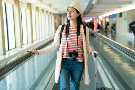 pretty woman standing on the walkway tunnel. the view of Taoyuan International Airport