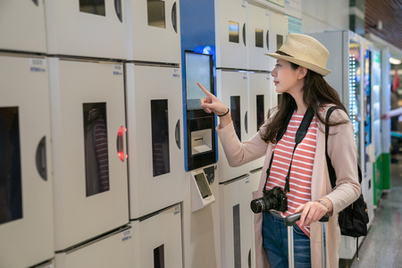 woman confirming intelligent coin lockers. trying to use one. view from side.