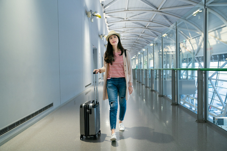 tourist carrying her luggage while walking.  looking up   and walking in the empty corridor.