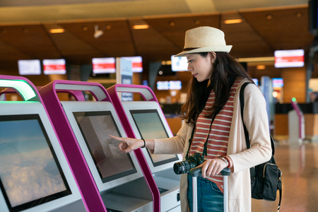 pretty asian visitor using self-service transfer machine in the airport. touching the screen and trying to check in successfully.