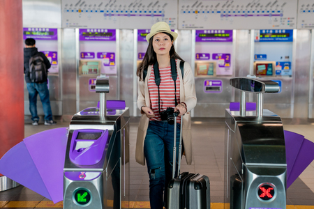 walking through the automatic ticket barrier. asian female carrying her belongings.