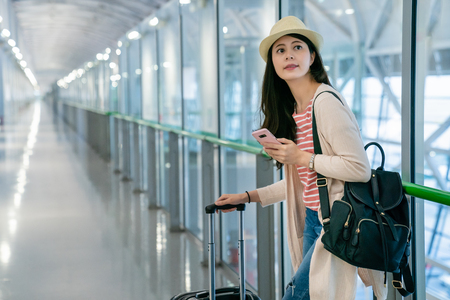 pretty asian woman leaning on the glass guardrail. looking somewhere else. holding and checking her phone.