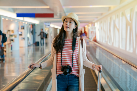 woman standing on the floor escalator walkway tunnel. by the background in airport. Stock Photo