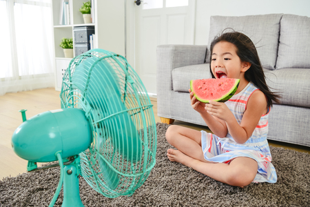 lovely girl eating melon with a big bite. sitting in front of a fan with legs crossed. cooling herself down from heat. Stock Photo