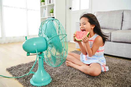 child eating watermelon with two hands. sitting in front of the electric fan.  taking a big bite delightfully. Фото со стока - 107566122