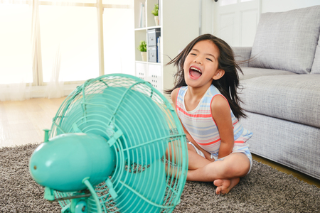 litle cute girl laughing and sitting in front of fan. refreshing herself from hot weather with legs crossed.