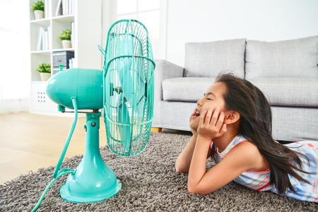 happy kid lying down in front of electric fan. with eyes clossed and hair blown by the breeze. half-body view from side.