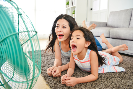 mother and child lying on the mat cheerfully. blowing their faces with electric fan.  laughing happily together. Imagens
