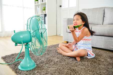 asian kid feeling cold while sitting in front of fan.  eating a sliced watermelon on the ground. with a frowning face. Stock Photo