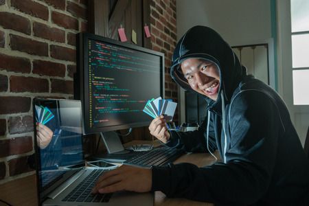 bad man showing the stolen credit card and breaking into the bank security system to get money.