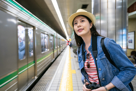charming travle female waiting for her train coming and holding her camera with a cheerful look. Stock fotó