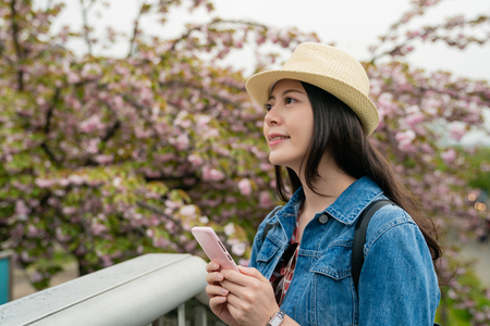 beautiful asian female using mobile in hands and looking enjoyable with a pretty smile in the park.