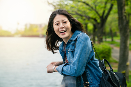 beautiful asian woman laughing with a pretty smile and leaning on guardrail next to river joyfully.