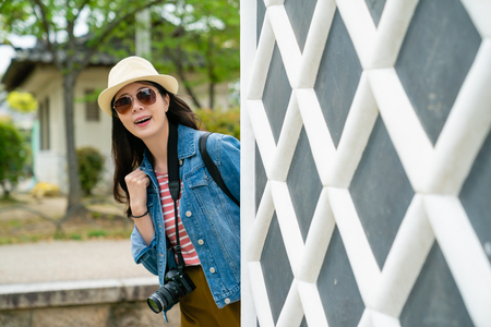 young stylish tourist smiling joyfully showing herself behind the whit grids wall in a famous sightseeing place.