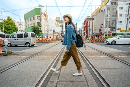 donna di viaggio rilassata che cammina attraverso la ferrovia che tiene il suo telefono nella città di osaka in giappone.